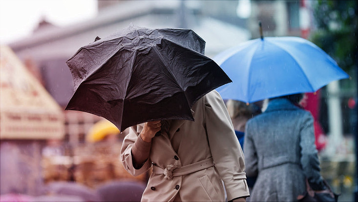 Menschen mit Regenschirmen im Wind