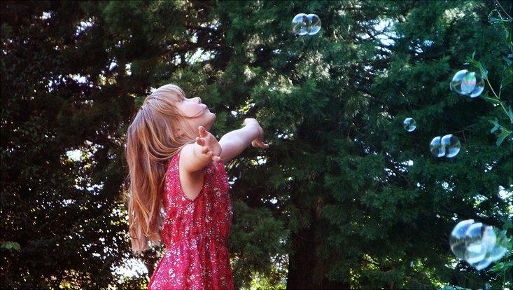 Ein Mädchen im geblümten Sommerkleid beim Spaß mit Seifenblasen auf dem Sommerfest 2018 des Fachbereichs Biologie.
