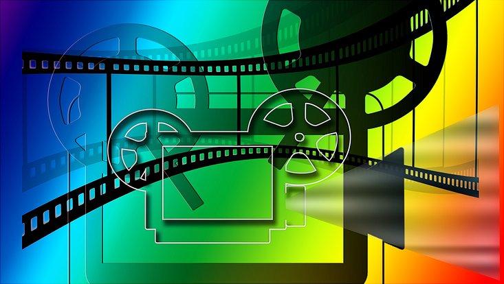 Ein Filmprojektor als Grafik auf regenbogenfarbenem Hintergrund