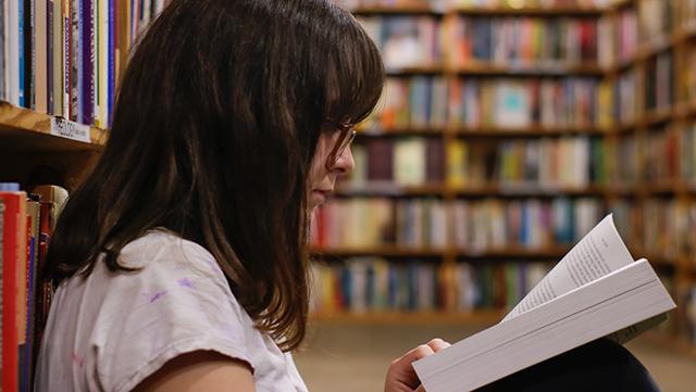 Frau sitzt in Bibliothek und liest.
