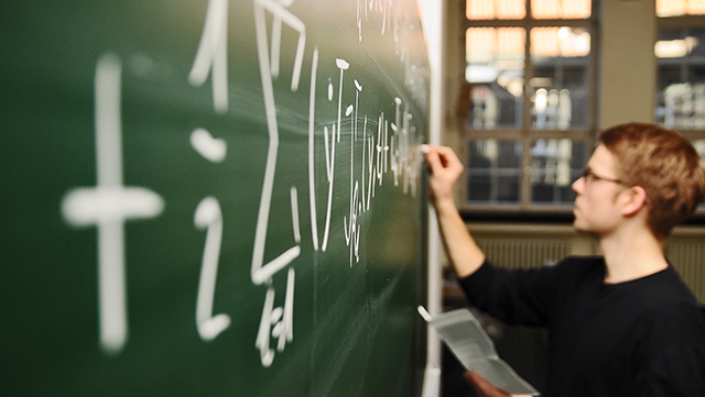 Student schreibt Formel an Tafel