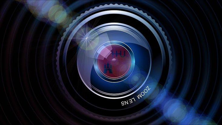Das Objektiv einer Kamera mit dem Spiegelbild des Logos der Universität Hamburg