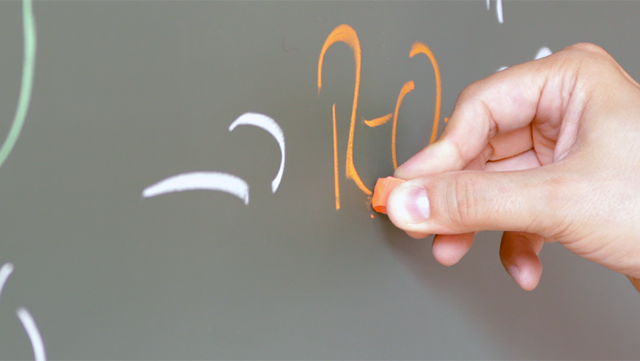 Hand schreibt an Tafel