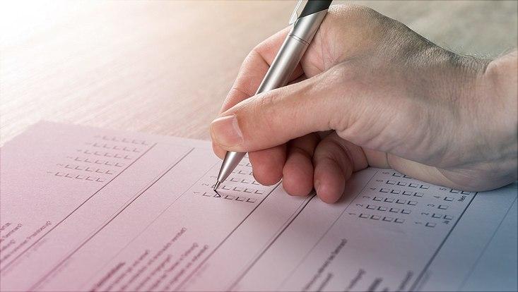 Hand mit Kugelschreiber die einen Umfragezettel ausfüllt