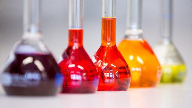 5 Messkolben gefüllt mit verschieden farbigen Flüssigkeiten
