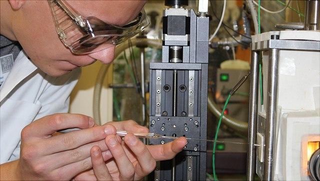 Studierender pipettiert eine Flüssigkeit in eine Reaktionskammer