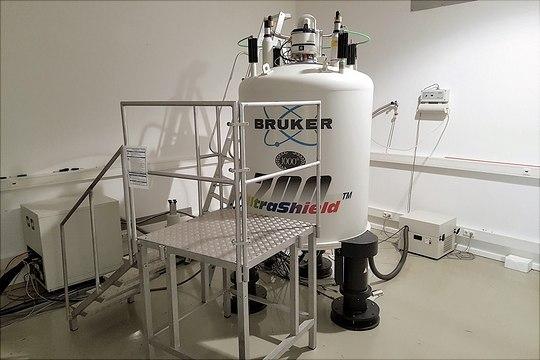 700 MHz NMR-Magnet mit Aluplatform in einem Raum vor weißer Wand