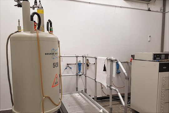 500 MHz NMR-Magnet mit Aluplatform und Konsole in einem Raum vor weißer Wand mit Pflanzen im Hintergrund