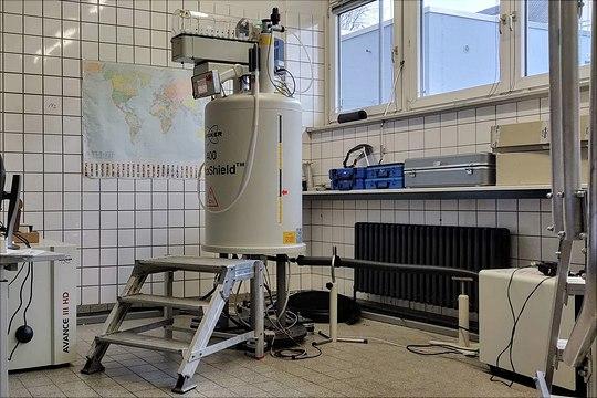 400 MHz NMR-Magnet mit Aluplatform in einem Raum vor gekachelter Wand