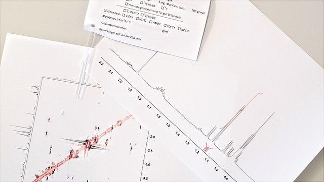 NMR-Spektren und eine NMR-Probe auf einem Tisch