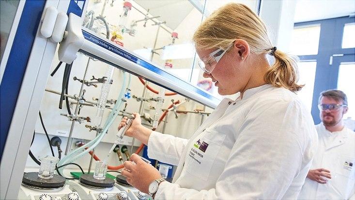 Schülerin bei der Synthese von Gold-Nanopartikeln: Zu einer Goldsäurelösung wird vorsichtig eine Trinatriumcitratlösung hinzugetropft.