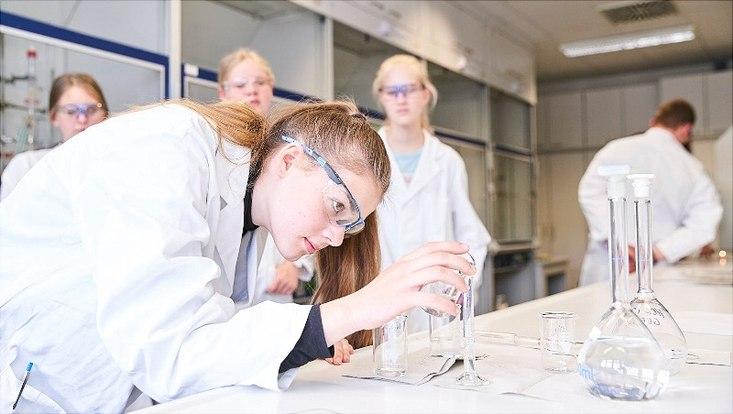 """Eine Schülerin beim Abmessen der Lösungen für den Versuch """"Der chemische Sonnenuntergang""""."""