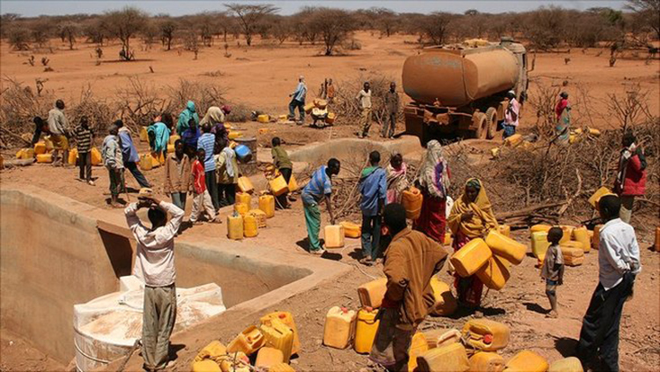 Viele Menschen in der Wüste mit gelben Wasserkanistern