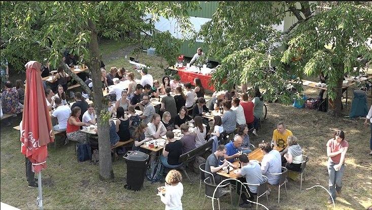 Viele Menschen sitzend unter den Kirschbäumen des Mensagartens