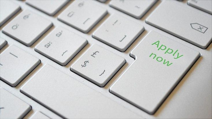 """Imagebild Bewerbung: Ausschnitt eines Keyboards mit grünem Schriftzug """"Apply Now"""" auf der Return-Taste"""