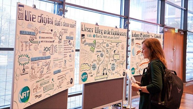 Konferenz-Teilnehmerin betrachtet Poster, die während der Tagung entstanden sind.