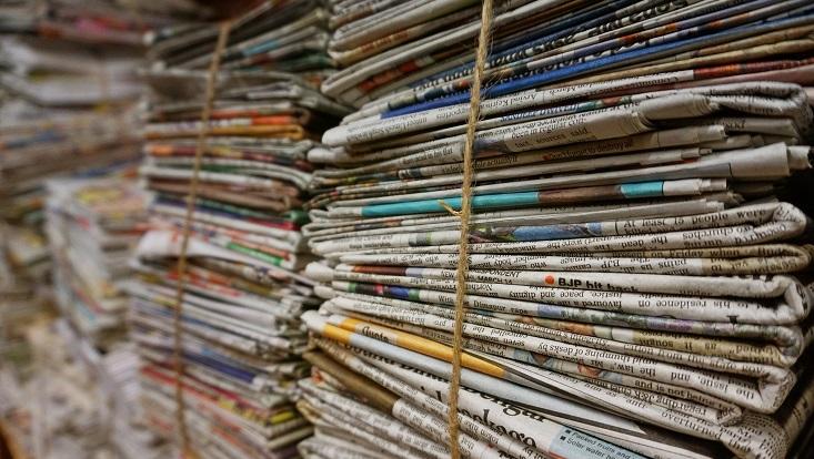 Aufgestapelte Zeitungen. Symbolisch für Klimakommunikation und Klimajournalismus.