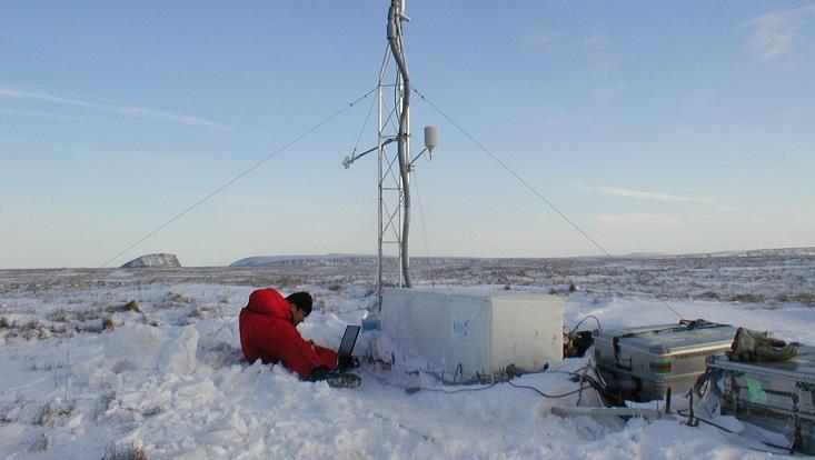 Ein Forscher in einem roten Schneeanzug sitzt im Schnee. Neben ihm eine Messstation. Symbolisch für Arktis, Permafrost und Meereis.