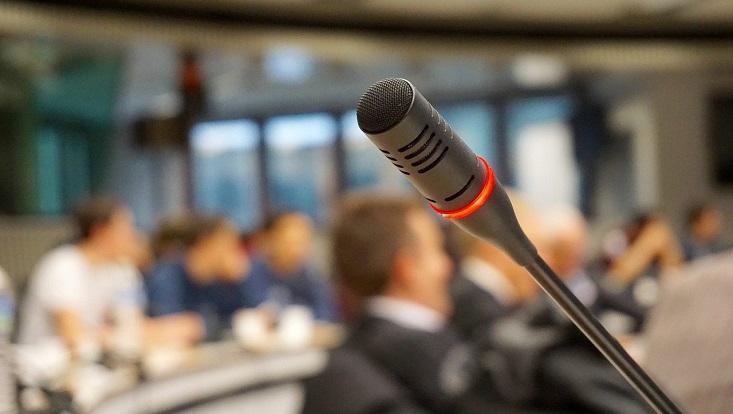 Im Vordergrund ein Konferenzmikrofon, im HIntergrund unscharfe Menschen.