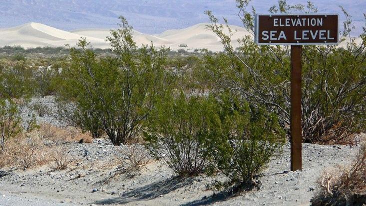 """Trockene Landschaft, im Vordergrund ein Holzschild auf dem """"Sealevel"""" steht."""