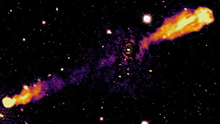 Die Abbildung zeigt kombinierte Aufnahmen von Daten, die mit Radioteleskopen und optischen Teleskopen aufgenommen wurden. Die feuerartigen Streifen in der Illustration sind sogenannte Jets, die weißen Punkte sind Sterne und Galaxien, die von Freiwill