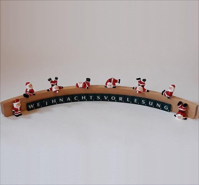 In einem Halbkreis mit Scrabblesteinen gelegtes Wort Weihnachtsvorlesung, auf dem einige Weihnachtsmänner herumtoben