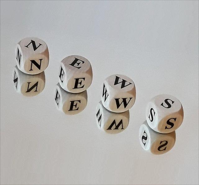 Würfel, die das Wort News buchstabieren, auf einer spiegelnden Oberfläche