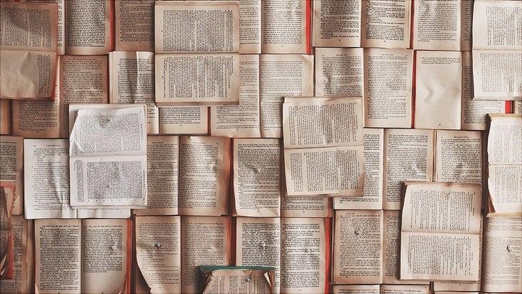Aufgeschlagene Textbücher, die an eine Wand gepinnt sind