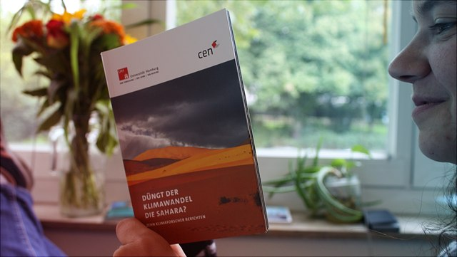 """Frau liest Booklet """"Düngt der Klimawandel die Sahara?"""""""