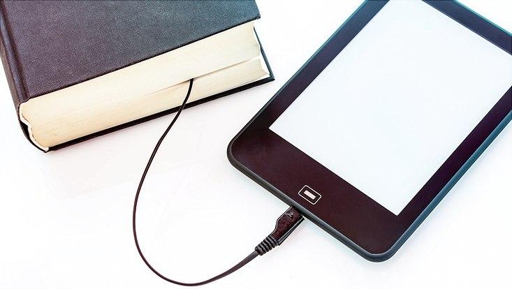 Buch und Tablet mit einem Kabel verbunden