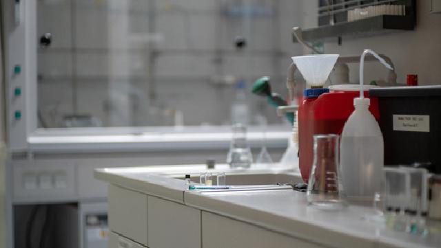 Labortisch mit rotem Kanister und verschiedenen Gläsern im Vordergrund und Chemikalienabzug im Hintergrund.