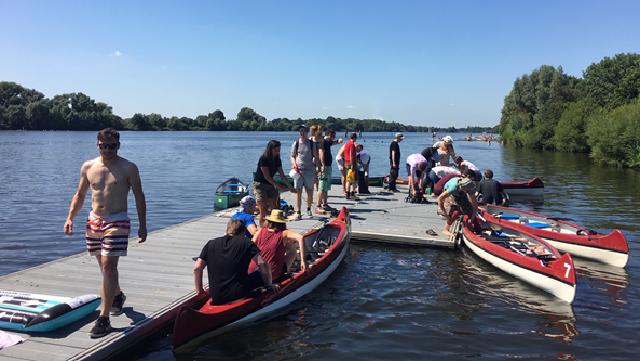 Holzsteg im Wasser, an dem drei rot-weiße Kanus angelegt haben und auf dem eine Gruppe von Menschen steht und sitzt.