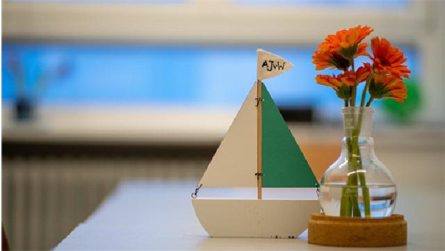Weiß-türkises Holzsegelschiff und Glasvase mit vier roten Blumen auf einem unscharf zu sehenden Tisch.