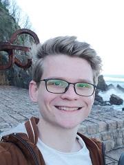 Porträt von Robin Stuhr mit Felsen und Strand im Hintergrund.