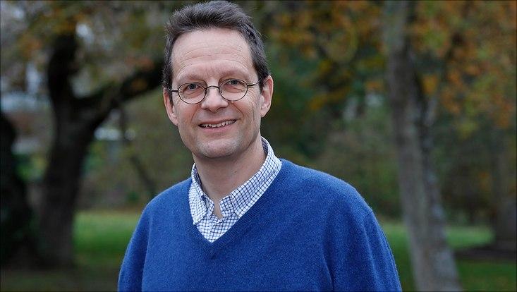 Mann in blauem Pullover vor grünem Hintergrund