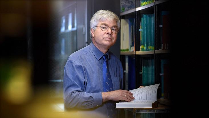Detlef Stammer in einer Bibliothek mit einem Buch in der Hand.