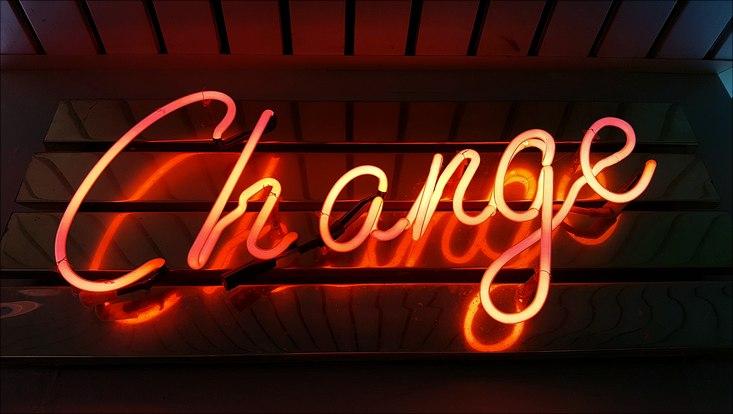 """Eine Neonröhre schreibt in Orange den Schriftzug """"Change"""" auf schwarzen Hintergrund"""