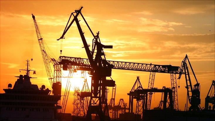 Silhouette von Kränen im Hamburger Hafen vor Sonnenuntergang