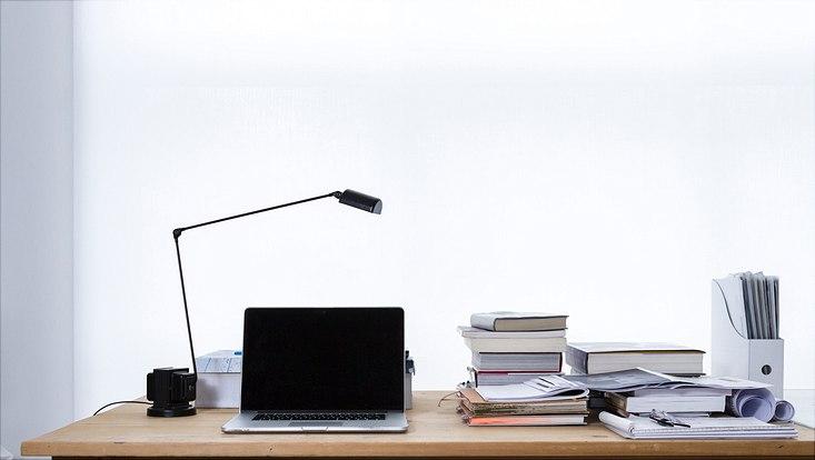 Schreibtisch mit Laptop und Büchern