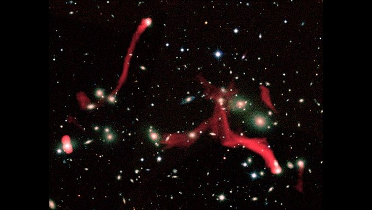 The filamentary structures observed by LOFAR at the center of Abell 2255, here reported in red. These radio emissions are due to trails of particles and magnetic fields released by the galaxies during their motion inside the cluster