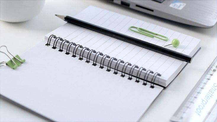 Schreibtisch mit Ringbuch und Bleistift