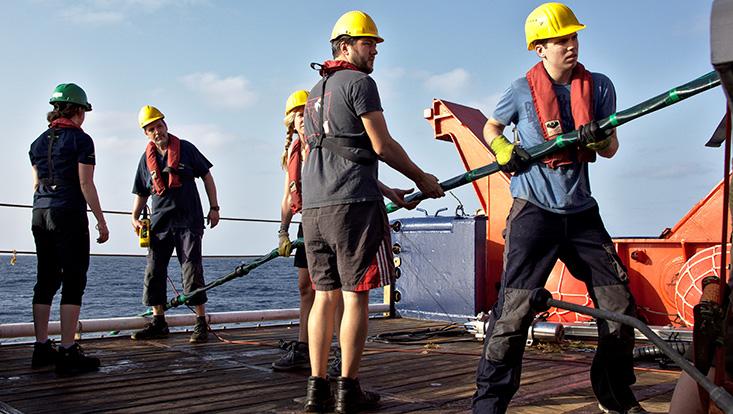 Forschende mit Sicherheitsuntensilien auf einem Schiff