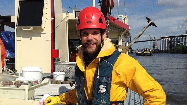 M. Spieckermann auf Forschungsbot, trägt roten Helm und gelbe Regenjacke