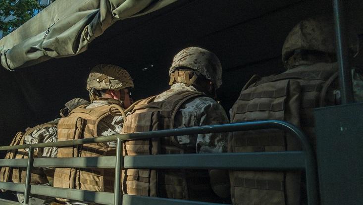 Menschen in Militäruniform sitzen mit dem Rücken zur Kamera auf einem offenen Fahrzeug.