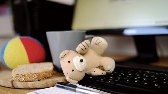 a teddy lying on a computer keyboard. A cup of tee and a piece of bread lying next to the keyboard