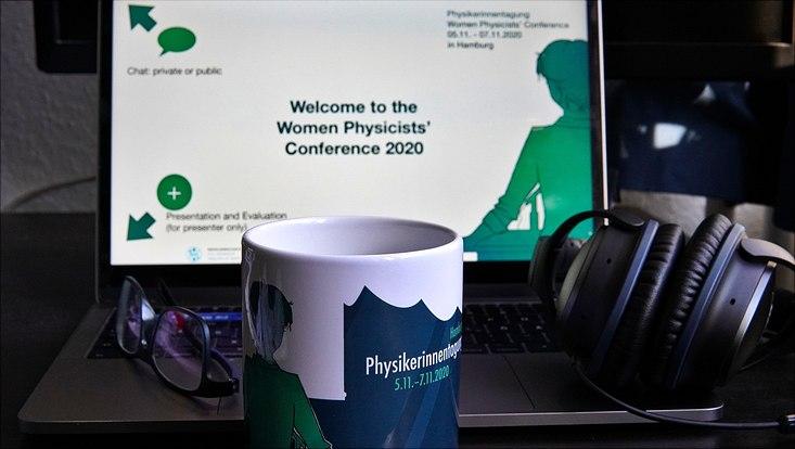 Foto eines Laptops mit einer Tasse mit Logo der Physikerinnentagung davor und Kopfhörern.