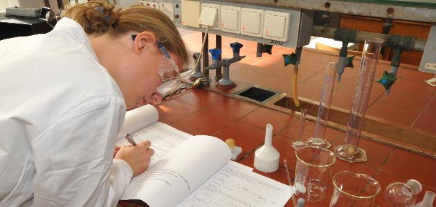 Schülerin im Chemielabor am Tisch mit Unterlagen