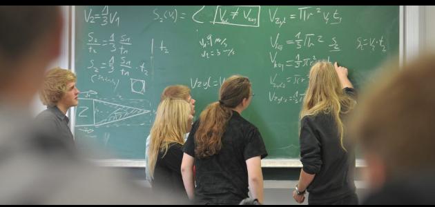 Schüler an Wandtafel mit mathematischen Berechnungen