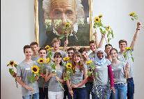 Schüler der Initiative NAT jubeln mit je einer Sonnenblume in der Hand vor einem Bild Albert Einsteins