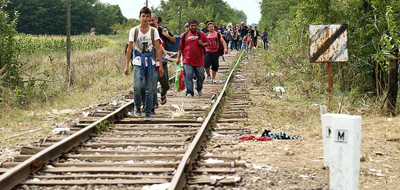 Menschen auf der flucht auf Bahngleisen